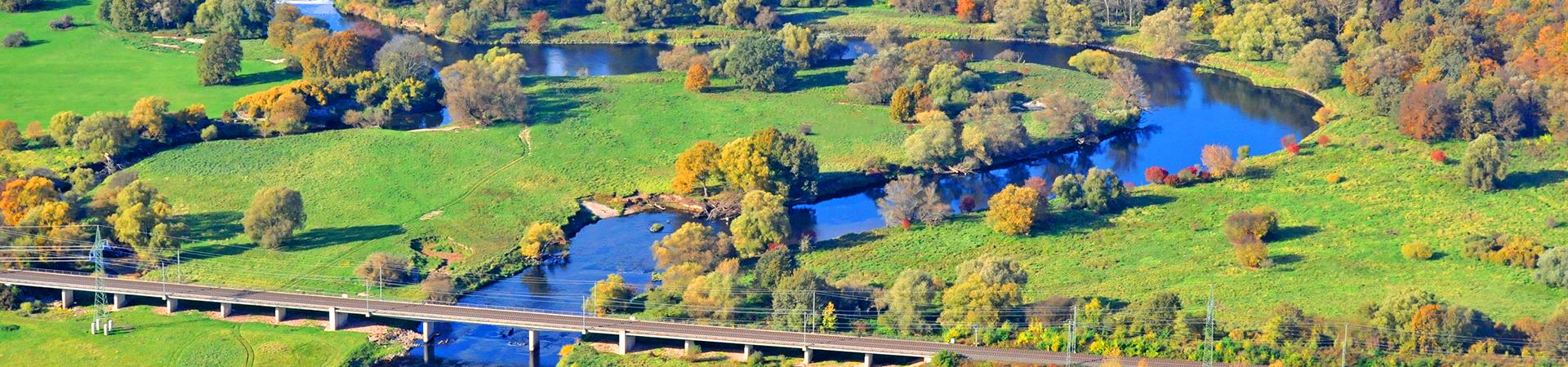 Die Mulde in ihrem Verlauf zwischen Friedersdorf / Muldestausee und Muldenstein (rechts im Hintergrund das Solarfeld auf de Gelände der ehemaligen Rohrfabrik Muldenstein), im Vordergrund die Bahnbrücke. Luftbild vom 24.10.2013